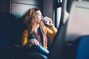 Girl drinking coffee on train